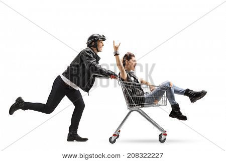 Biker pushing a shopping cart with a punk girl riding inside and making a rock sign isolated on white background