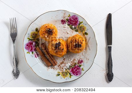 Pumpkin desert with cinnamon chocolate on plate with knife and fork on white wooden background
