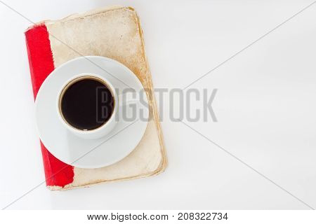 white cup of the coffee and vintage book isilated on white background.