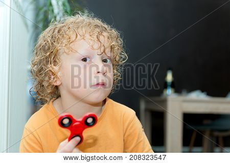 a little blond boy playing with hand spinner
