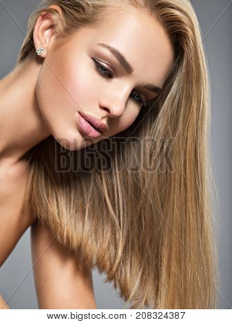 Portrait of  a beautiful young woman with long light straight  hairs and brown make-up.   Pretty gorgeous girl posing at studio.