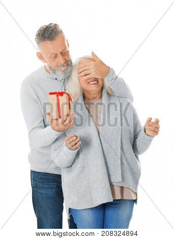 Senior man covering his wife's eyes and giving her Christmas present, on white background