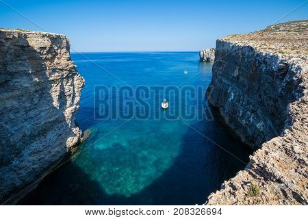 Exploring the dramatic huge cliffs and sea caves of east coast of Comino, over looking the deep azure crystal clear waters of the Mediterranean, Comino, Malta, June 2017