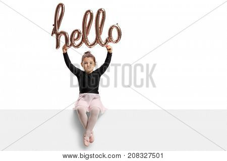 Small ballerina sitting on a panel and holding a hello sign isolated on white background