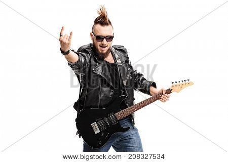 Punker with an electric guitar making a rock hand gesture isolated on white background