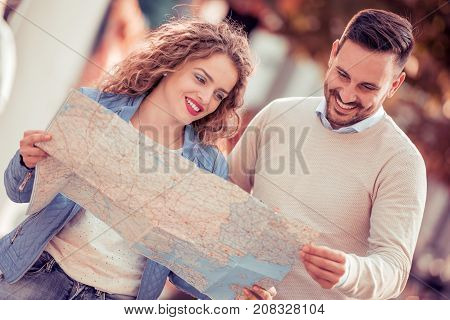 Loving couple with a map looking for an address on the strreet.