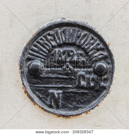 Geodetic sign (benchmark) cast-iron levelling mark in the wall of building