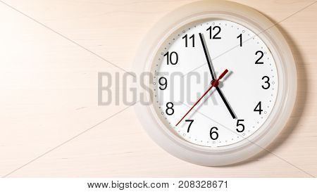 Clock hanging on wall ticking showing five hours