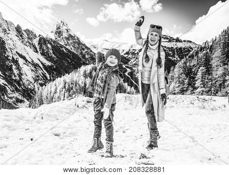 Winter on higher level of fun. Full length portrait of modern mother and daughter travellers in the front of mountain landscape in Alto Adige Italy playing snowballs poster