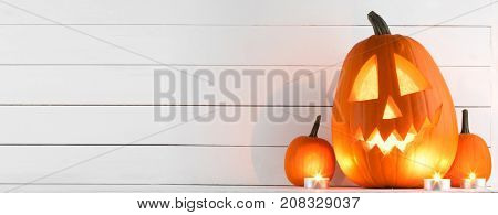 Halloween pumpkin heads jack o lantern and candles on white wooden background
