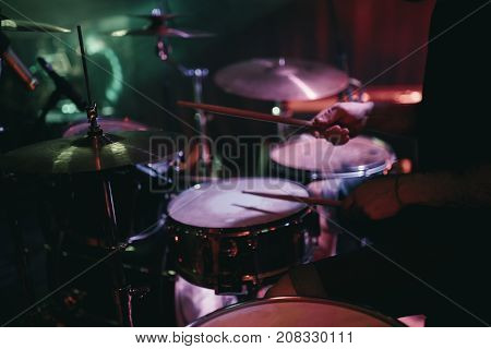 Drummer playing his drum kit on concert in club