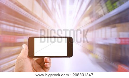 Businessman holding a smartphone in Warehouse industrial and logistics companies. The boxes on high shelves stocked. Motion blur effect. Bright sunlight.