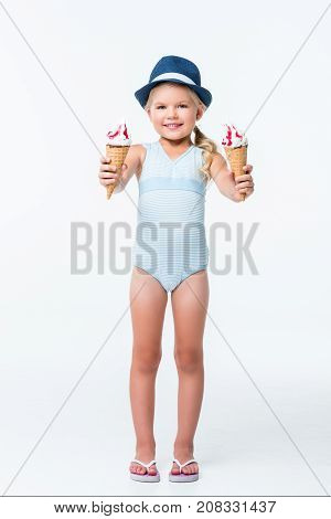 adorable little girl in swimsuit holding ice cream and smiling at camera