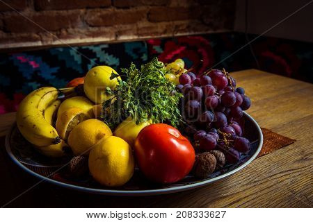 Delicious Fruits In A Plate On A Wooden Table