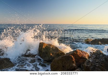 Ocean waves crushing into waves in sunset