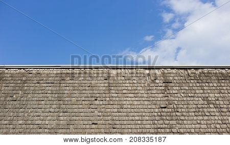 battered wooden shingle roof against a blue sky with clouds in landscape orientation