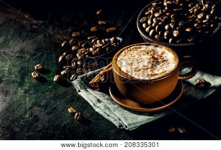 Background of composed coffee beans and mug with tasty cappuccino arranged on black surface.
