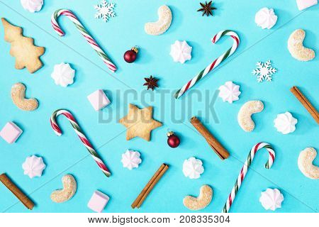 From above shot of assortment of sweets and candies composed with Christmas decor and cinnamon on blue.