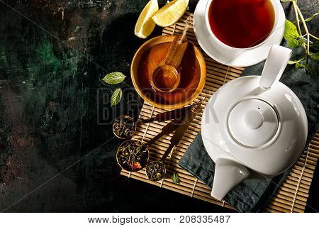 From above view of teapot and cup composed with various aromatic additives on black background.