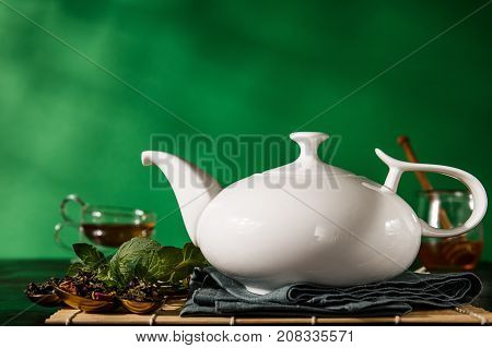 Beautiful composition of white ceramic teapot arranged with various tea additions on green background.