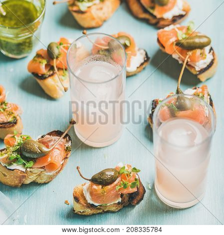 Crostini with smoked salmon, pesto sauce, watercress and capers and pink grapefruit cocktails in glasses over light blue background, selective focus, square crop. Party, catering or fingerfood concept