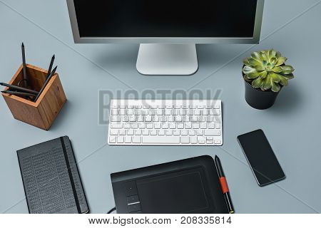 Wooden desk with laptop, notepad with blank sheet, pot of flower, stylus and tablet for retouching. Workspace of professional retoucher. Creativity, design, art and modern equipments concept