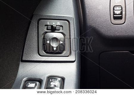 Car Mirror Control Button in car inerier background.