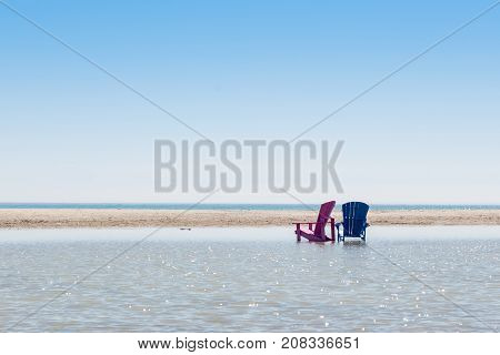 blue and magenta empty beach chairs standing in the water on a sunny day after a flooding