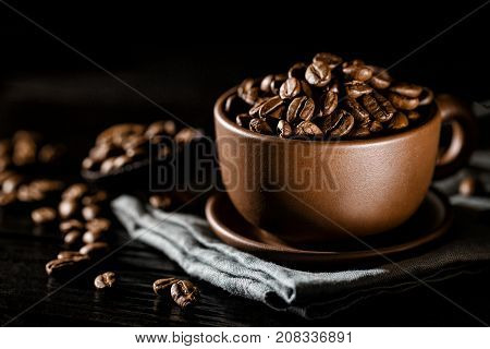 Close-up shot of brown cup composed on napkin and filled with aromatic coffee beans.