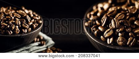 Composed view of two bowls filled with roasted brown coffee beans on black.