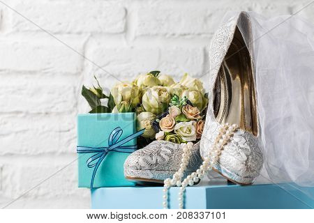 Creative arrangement of lace wedding shoes composed with accessories and flowers in studio.