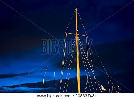 Sail masts  and ropes against night blue sky.