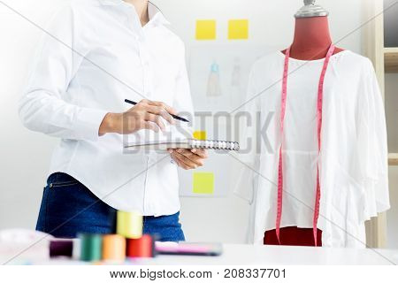 Asian tailor adjusts garment design on mannequin in workshop make a little adjustment to her work on model in the studio