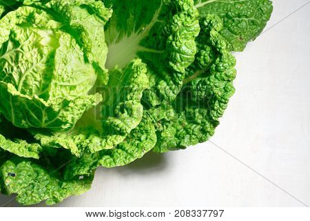 Background with a big fresh cabbage on white wooden background closeup