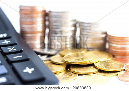 Coins stack with a calculator on white background. The concept of business growth financial or money savings with copy space for text.