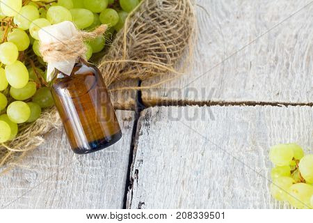 Healing grapes seeds oil in a glass jar fresh grapes on old wooden background seed extract has antioxidant and nourishing the skin spa concept on white wooden background. Bio eco products.
