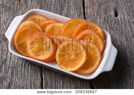 An rectangle serving plate of dried sweetened orange slices on a rustic wood surface.