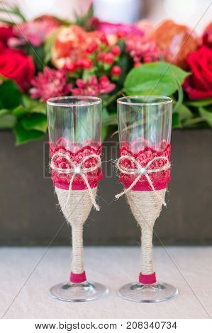 decorated champaign Glasses on the table with red flowers on background