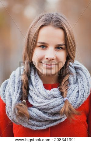 Beautiful teen girl with two pigtails in a red coat in autumn park