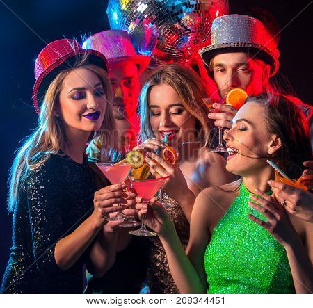 Cocktail party with group people dancing and drink cocktail. Happy women in evening dresses and men have fun in night club and disco ball background. Rest after a hard day at work.