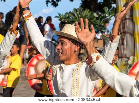 Dumaguete Philippines - 16 September 2017: Sandurot Festival dancer in grass hat. Carnival actor dancing in colorful costumes. Sunny day parade in Philippines. Autumn harvest celebration