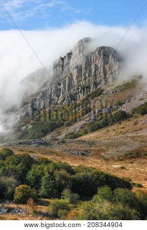 Mountains in the clouds. The 'Eklizi-Burun' peak in clouds - one from highest peaks Crimean mountains. Early autumn.