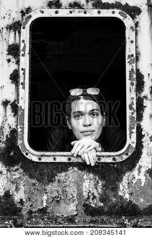 Black and white portrait of a young woman in an abandoned wagon train.