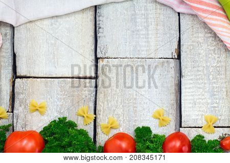 Italian food cooking-tomatoes basil pasta peppers and tomato on woden background top view copy space.