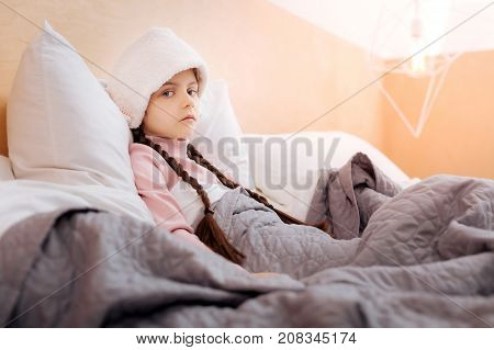 Tired glance. Little ill sad girl looking tired while sitting with a wet towel on her forehead and a warm blanket on her legs