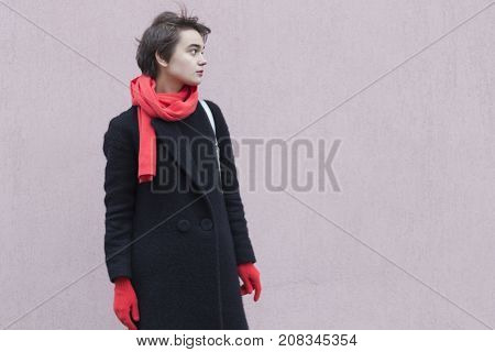 Dramatic Portrait Of Young Melancholy Woman In A Red Scarf And Gloves Against Cocrete Wall. Concept