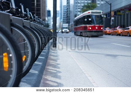 Toronto streetcar in the distance coming down a street with parked taxis and a row of wheels and bikes at a rental station - public transportation