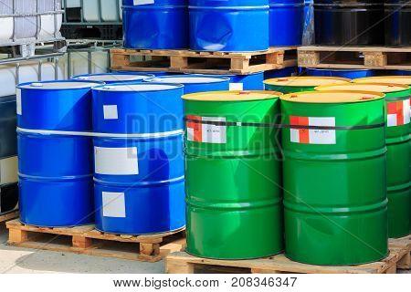 Big Green And Blue Barrels On Wooden Pallets