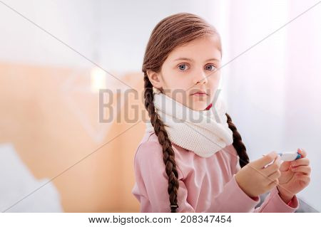 Responsible girl. Nice little girl with big grey eyes sitting on the bed and holding carefully a thermometer before measuring the temperature