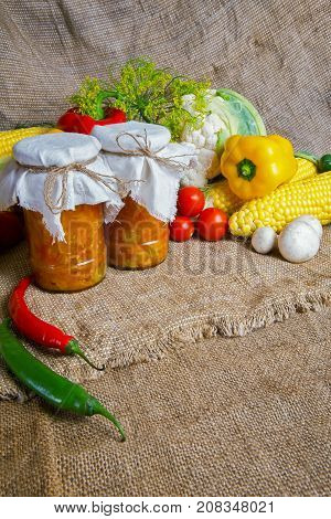 jars with winter supplies, banks with salad are on the table with vegetables